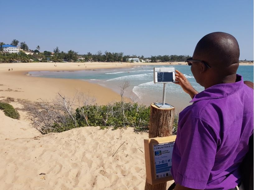 "Dr Ernesto Macaringue taking the first photo ""snap"" from the CoastSnap station in Tofo beach (#coastsnaptofo)"