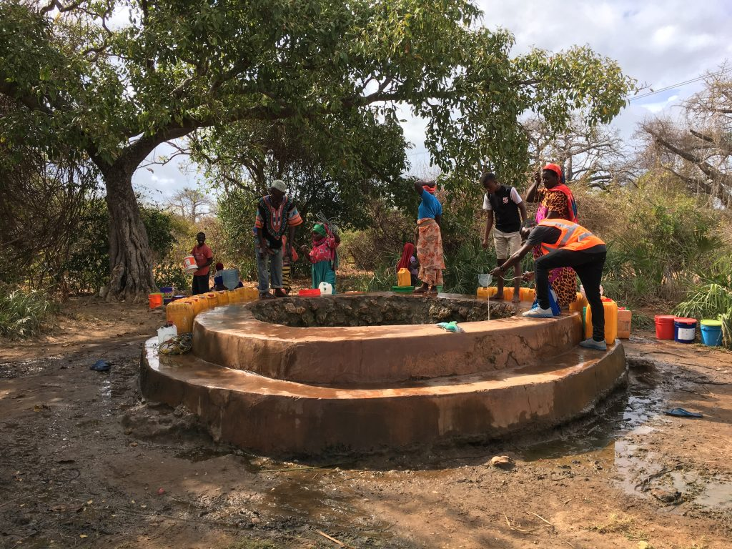 Javern Tenga (with an orange reflector), a student from the University of Dar es Salaam measuring the water-depth at the great-well—the main water supply in the Island