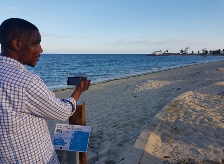"Leovigildo Cumbe taking the first photo ""snap"" from the CoastSnap station in -Praia de Miami-, the east site of the island (#coastsnapilha)"
