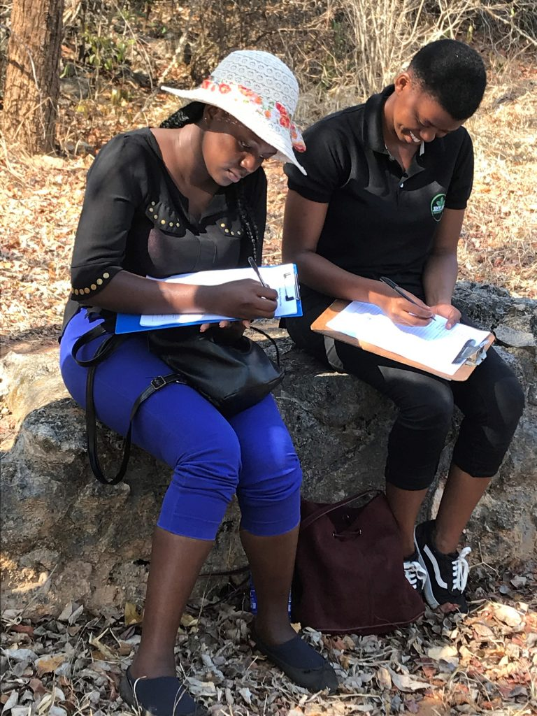Neema Munisi (left) and Irene Reuben (right) filling well survey forms