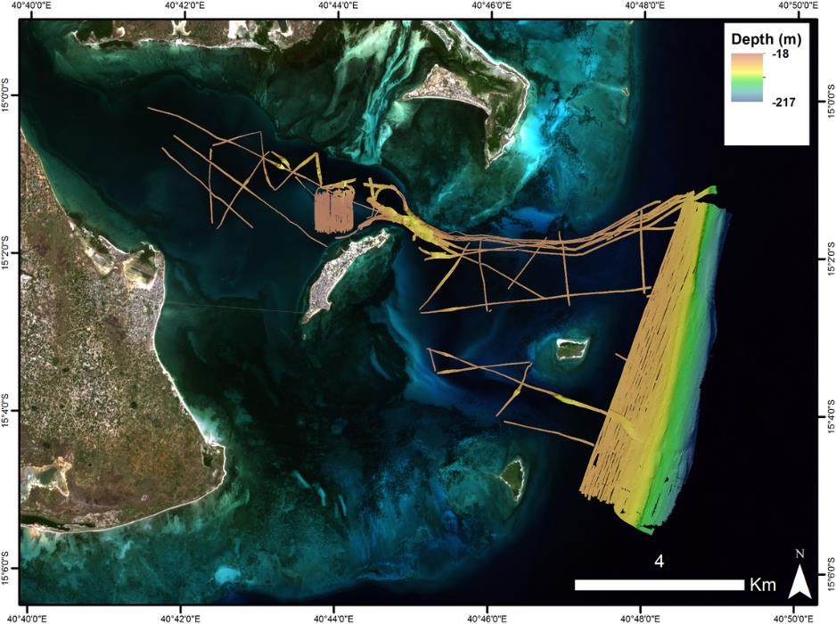 Survey tracks and colour-coded multibeam imagery of the seabed in the environs of Mozambique Island superimposed onto a recent Sentinel-2 satellite image. Warm colours indicate shallow water, shading to colder colours for deeper water